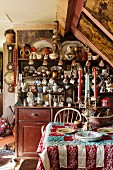 Patchwork quilt and candelabra on table in front of dresser crammed with crockery and flea-market finds