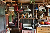 Vintage kitchen with cooking utensils hung up and cluttered shelves