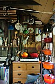 Cooking utensils on shelves and hung on walls in rustic kitchen