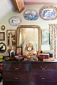 Table clock and vintage mirror on top of wooden chest of drawers below decorative plates on wall