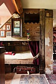 Bunk beds made from reclaimed wood and antique wall clock in vintage interior