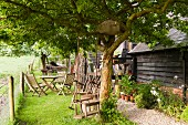 Garden furniture and swing outside wooden house