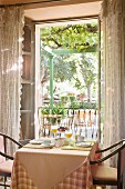 Small breakfast table in front of open French windows with view of terrace