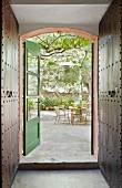 Offene grünlackierte Fenstertür mit Blick auf sommerlichen Terrassenplatz im Innenhof, im Vordergrund metallbeschlagene dunkelbraune Wandschränke