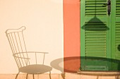 Schattenwurf von Stuhl und Tisch auf Hausfassade neben grünen Lamellentür