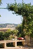 Blick von Terrasse über schlichte Steinbank mit Rankbogen in sommerliche mediterrane Landschaft