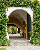 Arched entrance with vaulted ceiling in ivy-covered villa façade