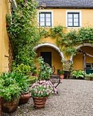 Patioartiger Innenhof einer gelb gestrichener Villa mit Arkaden, im Vordergrund Blumentöpfe auf Kiesboden