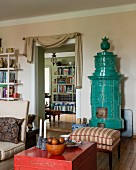 Red, Chinese wooden trunk and stool with striped upholstery in front of antique turquoise tiled stove