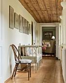 Stuhl und skandinavische Sitzbank in schmalem Gang mit rustikaler Holzdecke