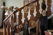 Collection of hats on wooden balustrade and traditional hatstands in background