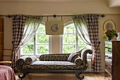 Antique chaise longue with ikat upholstery in front of arched windows with gathered curtains