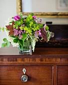 Gartenblumenstrauss in Glasvase auf Holzkommode