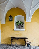 Rustic wooden bench against yellow-painted wall below bouquet in niche in passageway with white vaulted ceiling