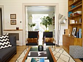 View across coffee table to fifties-style black armchairs and standard lamp in front of open double doors