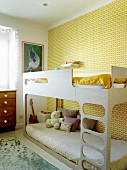 Bunk beds against wall with yellow retro-patterned wallpaper in children's bedroom