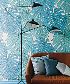 Brown leather sofa and classic floor lamp in front of wallpaper with turquoise philodendron motifs