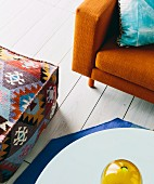 Orange-colored retro sofa, ethnic pouf and coffee table on white plank floor