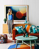 Blue patterned cushions with ethnic print on orange sofa and young woman in sunglasses in front of photo picture