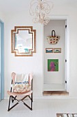 Chair with wooden frame and pink cover next to open door and view of wall with hanging basket bag