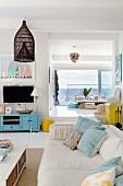 weiße Couch mit türkisblau gemusterten Kissen in hellem Wohnraum mit Meerblick