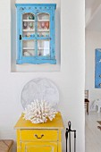 White coral on a yellow vintage box, light blue vintage display cabinets above in wall niche