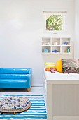 Light blue patent leather sofa, in front of it blue and white striped carpet with floor cushions next to the cot