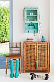 Vintage wall cupboards and rattan sideboards next to bamboo chairs and turquoise rubber boots in a summery atmosphere