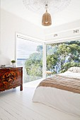 Double bed next to floor-to-ceiling corner windows with panoramic views and ethnic cabinets on white floorboards