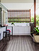 Slatted wall above outdoor kitchen on roofed wooden terrace