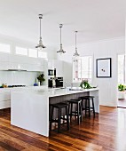 Stools at kitchen counter below retro pendant lamps in open-plan kitchen with white fronts and parquet floor