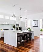 Hocker an Kochinsel mit Retro Pendelleuchten, offene Küche mit weissen Fronten und Parkettboden