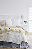 Fur cushion and blanket with woollen pompoms on bed in light-flooded bedroom