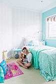 Girl playing guitar sitting next to bed with mint-green crocheted blanket in bedroom in pastel shades