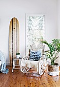 Rocking chair, surfboard and house plant in paint-dipped basket in exotic seating area