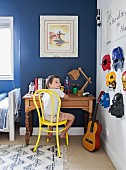 Boy sitting at desk in bedroom with super-hero masks hung on wall