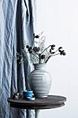 Trockenblumen in gestreifter Keramikvase auf rustikalem Bistrotisch vor Vorhang