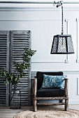 Armchair made of rustic wooden frame and black upholstery, pendant lamp hanging on a rod above