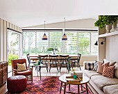Living room in a beach house with a dining table by the window and a seating area with a pattern mix carpet