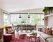 Wohnraum in Strandhaus mit Esstisch am Fenster und Sitzbereich mit Mustermix-Teppich