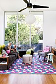 Corner sofa and retro armchairs on colourful rug with graphic pattern in front of floor-to-ceiling windows overlooking garden
