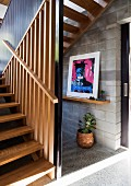 Dog-leg stairs with wooden slatted side wall and modern artwork on grey concrete-block wall of hallway