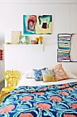 Colorful bedroom with pictures and different patterned pillows and bedspread