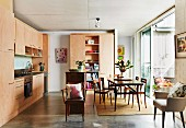 Eat-in kitchen with light wooden fronts, dining area and large, open patio door