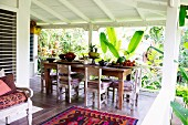 Dining table with simple wooden chairs and fruit bowls on a wooden terrace in a tropical setting