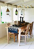 Crystal chandelier over rustic dining table with Balinese batik runner and ethnic-style crockery