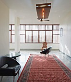 Retro leather armchairs on Oriental rug in purist interior; subdued light falling through sunscreens on continuous strip of windows