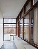 Corridor in modern Indian house with continuous, wood-framed glass wall
