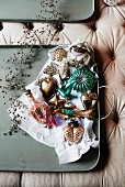 Olive-green tray of vintage-style Christmas decorations on upholstered surface