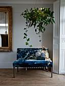 Mit Blättern und Efeu festlich drapierte Pflanzenampel über elegant gepolsterter Sitzbank mit Weihnachtsdeko